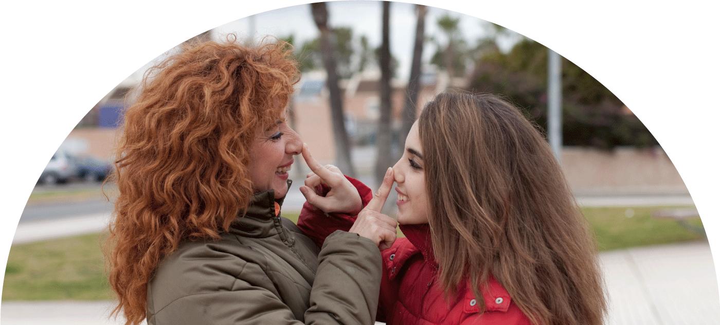 Acogida familiar, mujer adulta y mujer joven en actitud cariñosa tocándose la nariz
